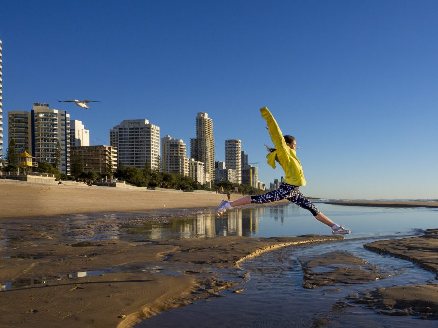 The Photo Coach -girl jumping over water at Surfers Paradise -Olympus camera