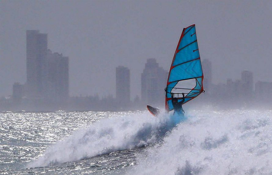 windsurfer with a blue sail rides a wave