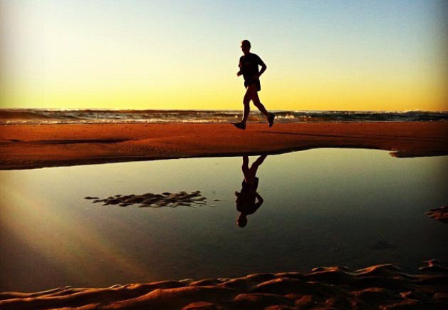 man running on the beach with reflection