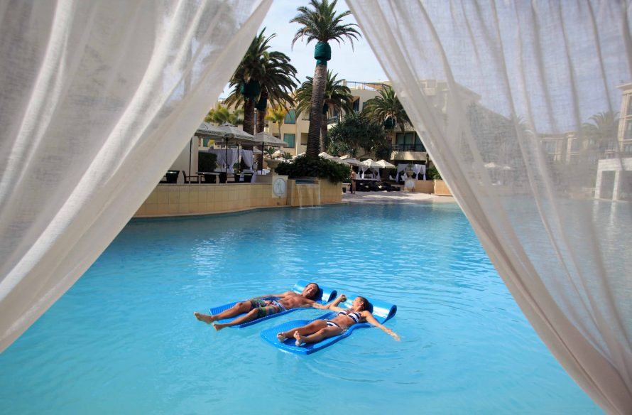 two people on airbeds in a swimming pool framed with curtains