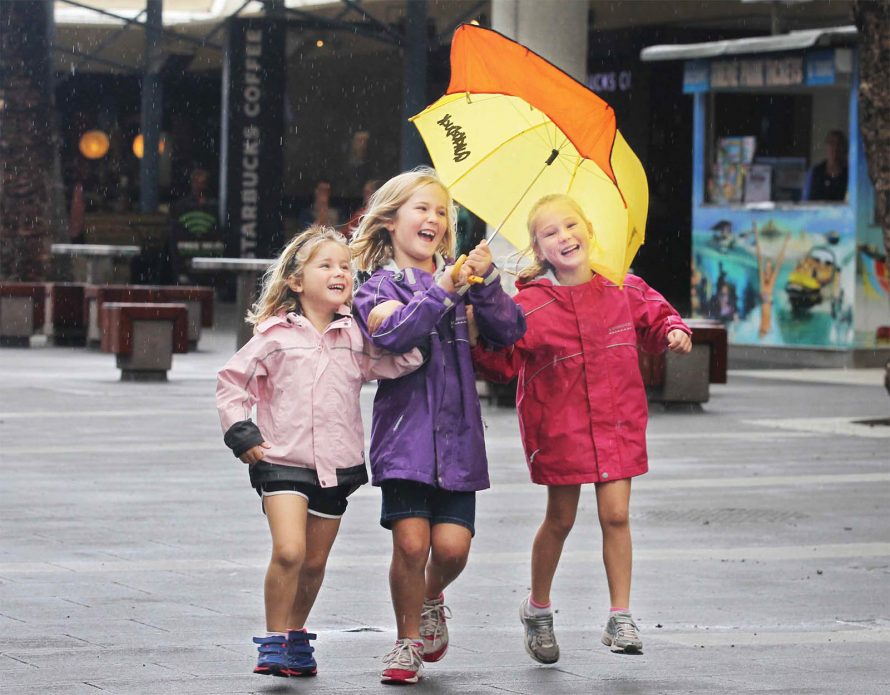 three little girls laugh under an umbrella