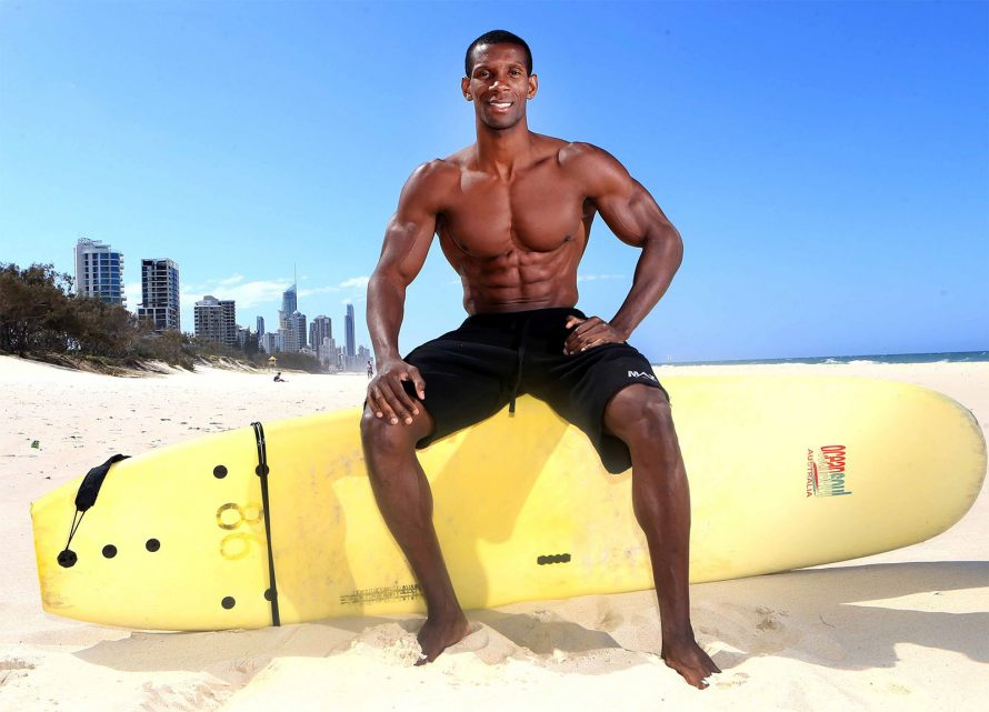 muscled man sitting on a surfboard on a beach