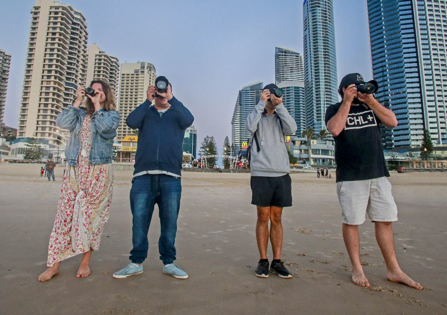 Four people in a line taking photos with digital slrs with Surfers Paradise in the background
