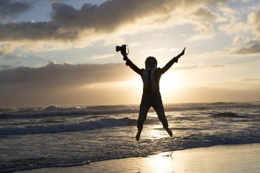 a lady jumps in the air on the beach silhouetted by the sun
