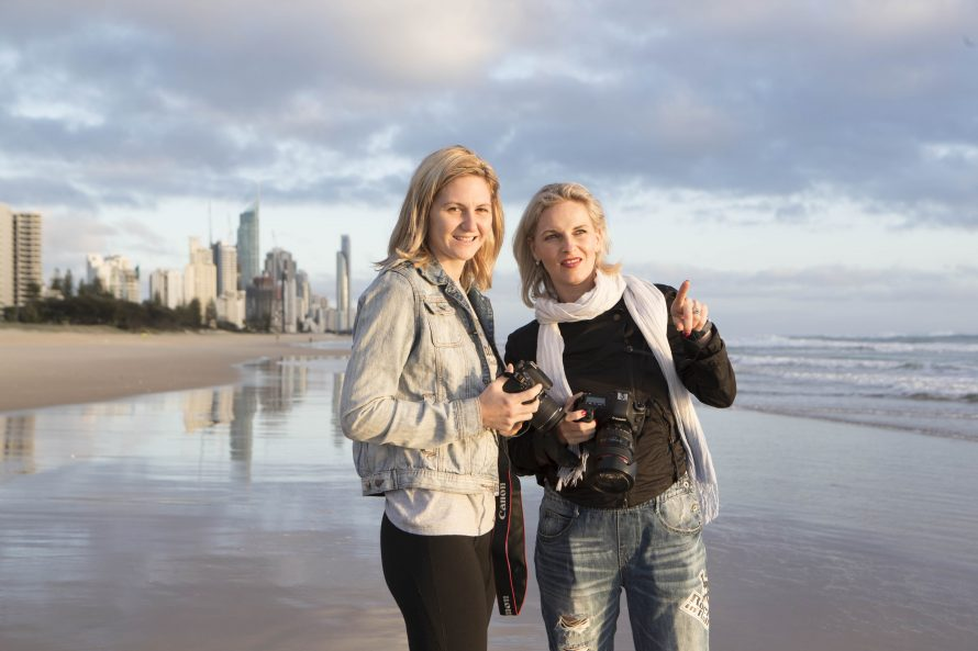 two women holding cameras look down the beach