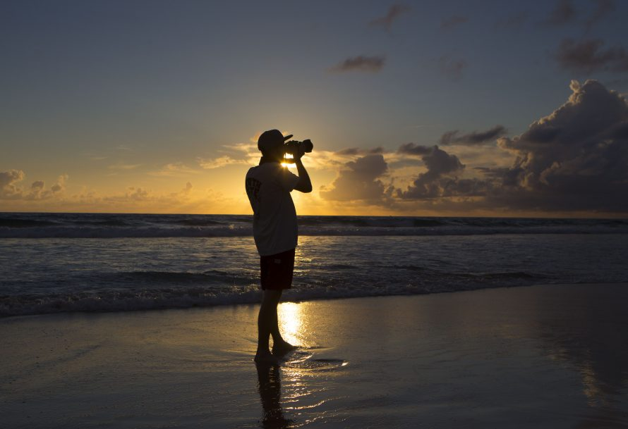 A person taking a photo on a Gold Coast Beach silhouetted against the sun